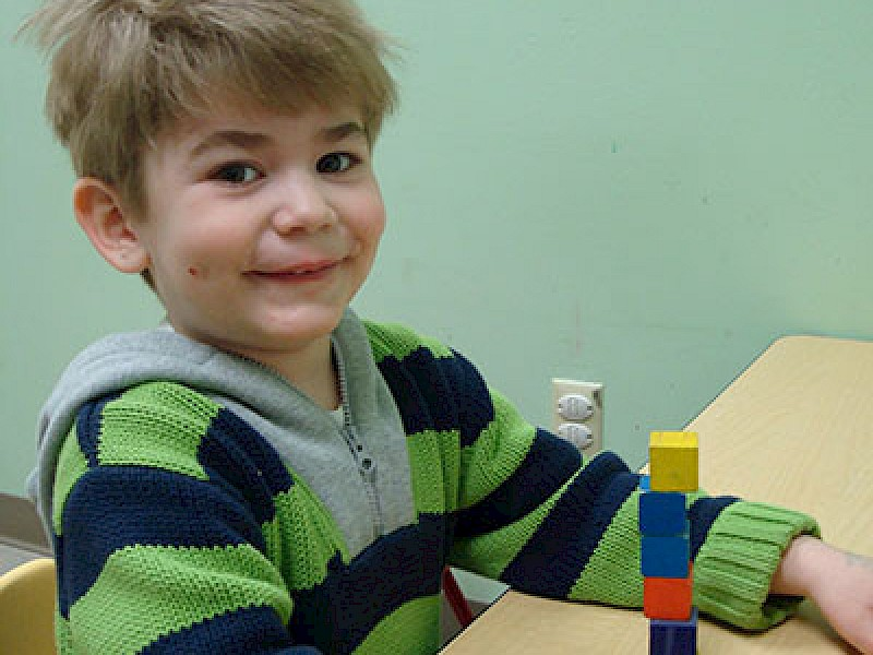 Child Smiling with Blocks